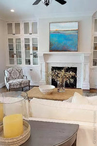 "Large coastal abstract beach wall decor ""Silver Sands,"" original art by Victoria Primicias, hangs above the fireplace."
