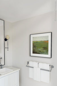 "Green abstract landscape art ""Spring Envy,"" wall art print by Victoria Primicias, decorates the bathroom."