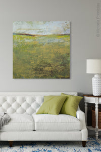 "Yellow green abstract ocean wall art ""Tender Reasons,"" digital print landscape by Victoria Primicias, decorates the living room."
