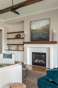 "Contemporary abstract seascape painting ""Titian Tides,"" digital artwork by Victoria Primicias, decorates the fireplace."