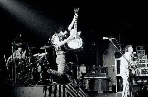Mick Jones of The Clash in mid-air at the Brixton Fair Deal