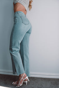 Light blue denim highwaisted jean. Tightly fited at the top and slightly wide leg at the bottom. Has 4 pockets, 2 slits on the outer seams and a raw hem.