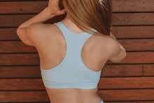 Load image into Gallery viewer, Baby blue sports bra with removable padding, plunge neckline and box label in the centre band located at the bottom of the crops centre front..