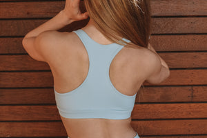 Baby blue sports bra with removable padding, plunge neckline and box label in the centre band located at the bottom of the crops centre front..