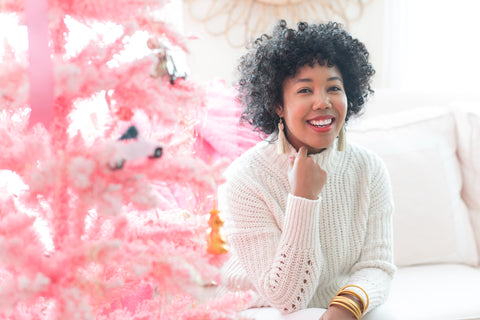 Black woman wearing white turtle neck sweater sitting next to pink Christmas tree with ornaments