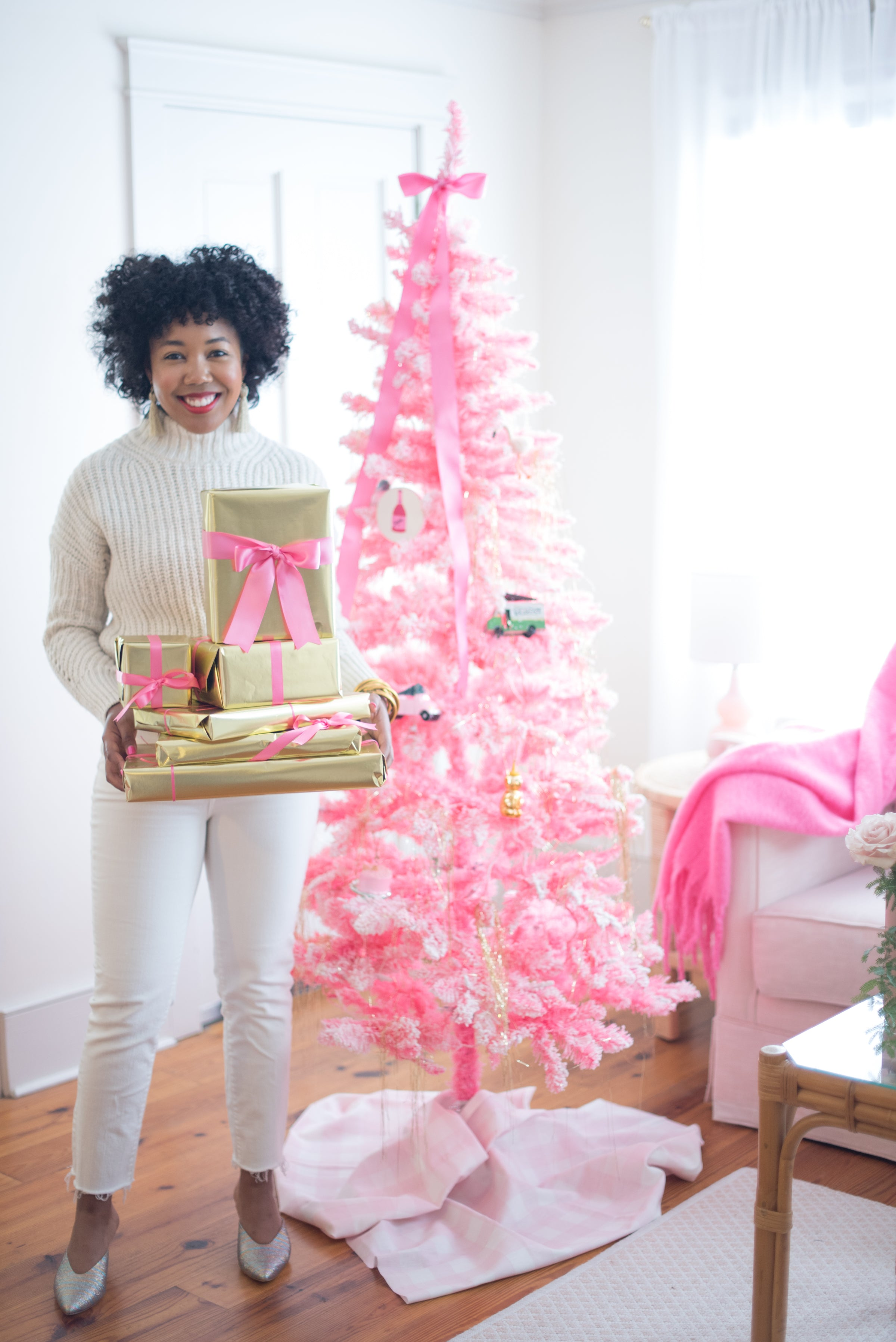 Black woman in a white sweater and white jeans holding gifts wrapped in gold paper and hot pink ribbon