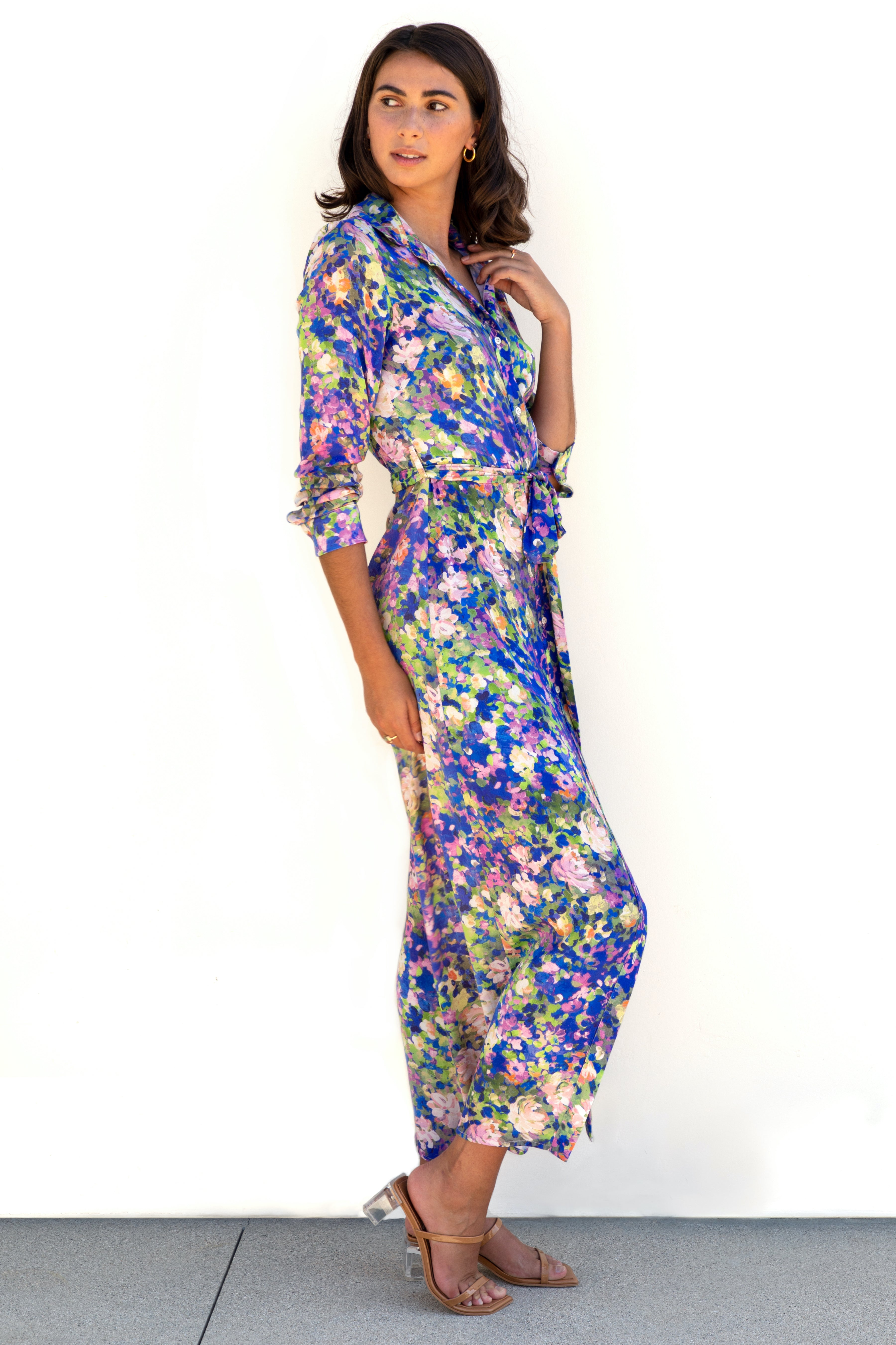 Full body side profile of model wearing Finchley Camino's maxi length blue floral collared button down dress with long sleeves rolled up to elbows