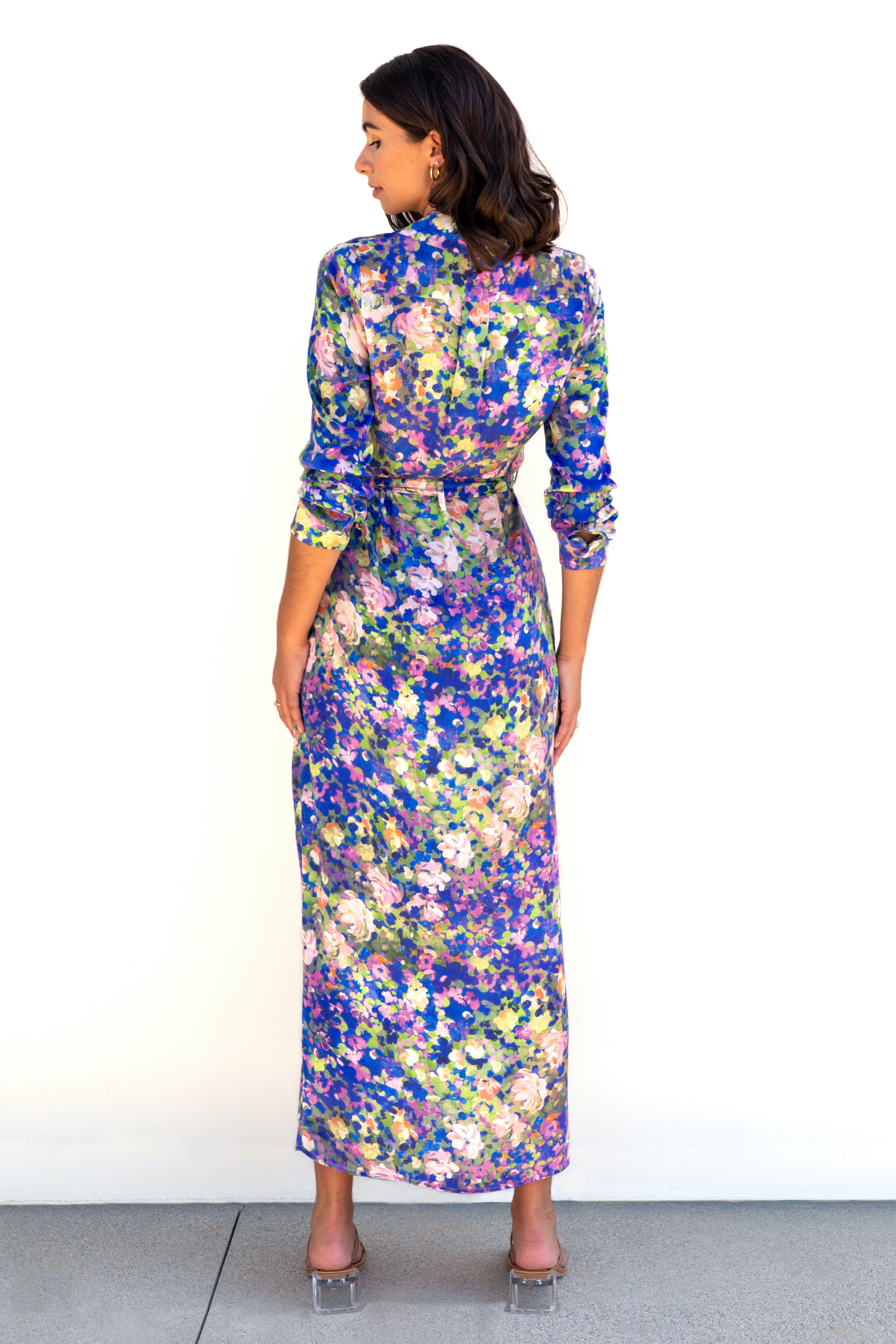 Back of model wearing Finchley Camino's maxi length blue floral collared button down dress with long sleeves rolled up to elbows