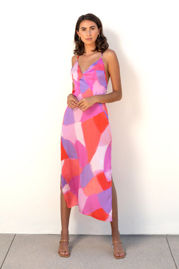 Model wears Los Angeles fashion brand Finchley Camino's pink abstract print midi length silk slip dress