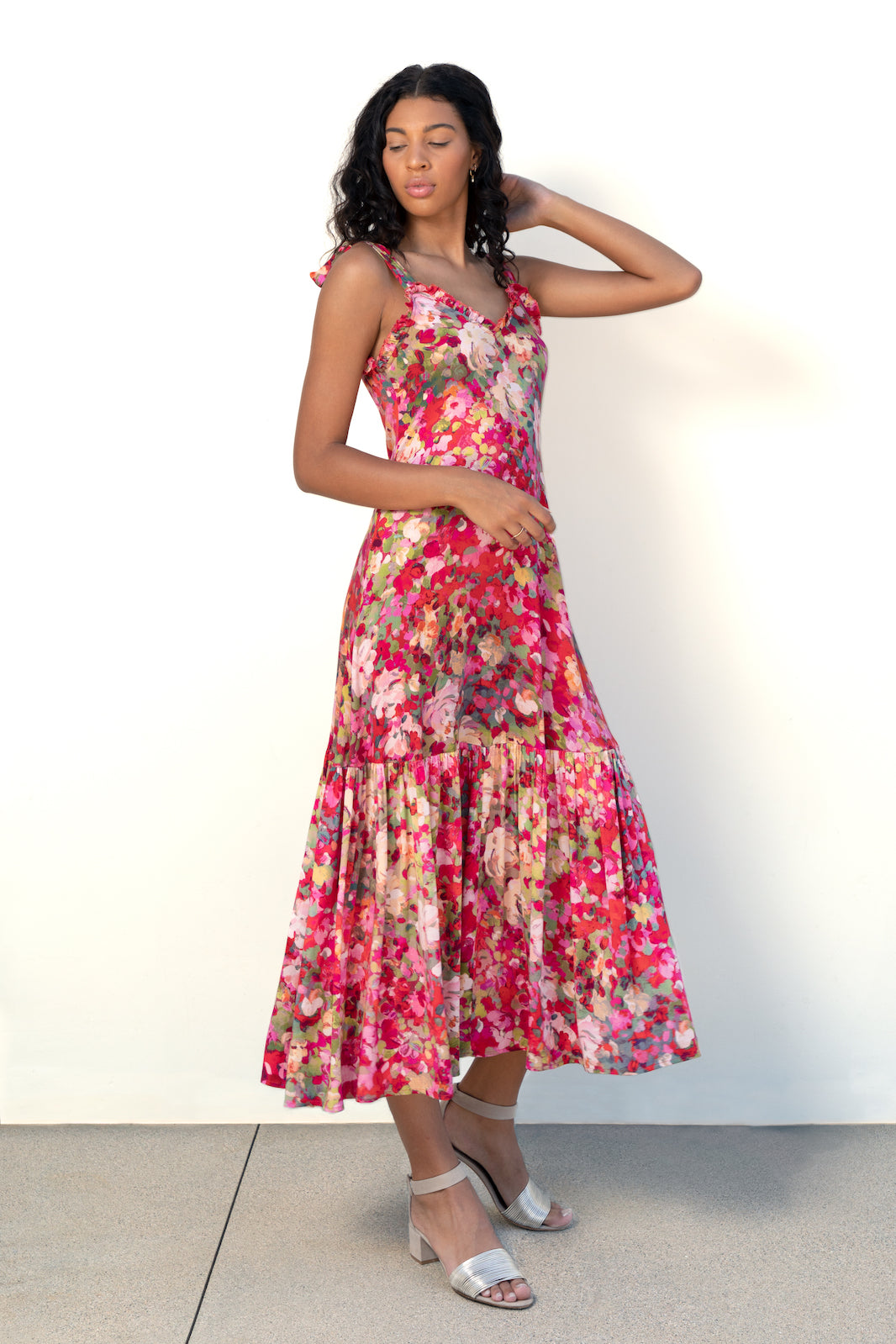 Model wears Finchley Camino's red floral printed maxi length dress with large ruffle hem