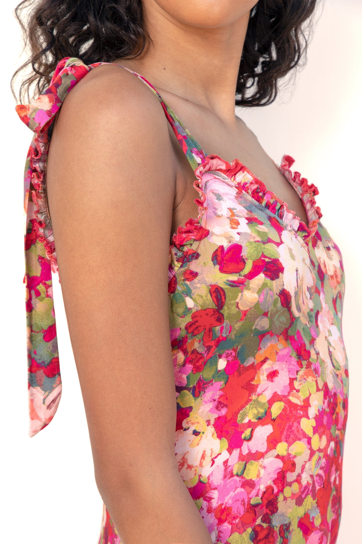 Close up of model wearing Finchley Camino's red floral dress with a sweetheart neckline with a ruffle trim and thick straps tied in two bows at the top of the shoulders