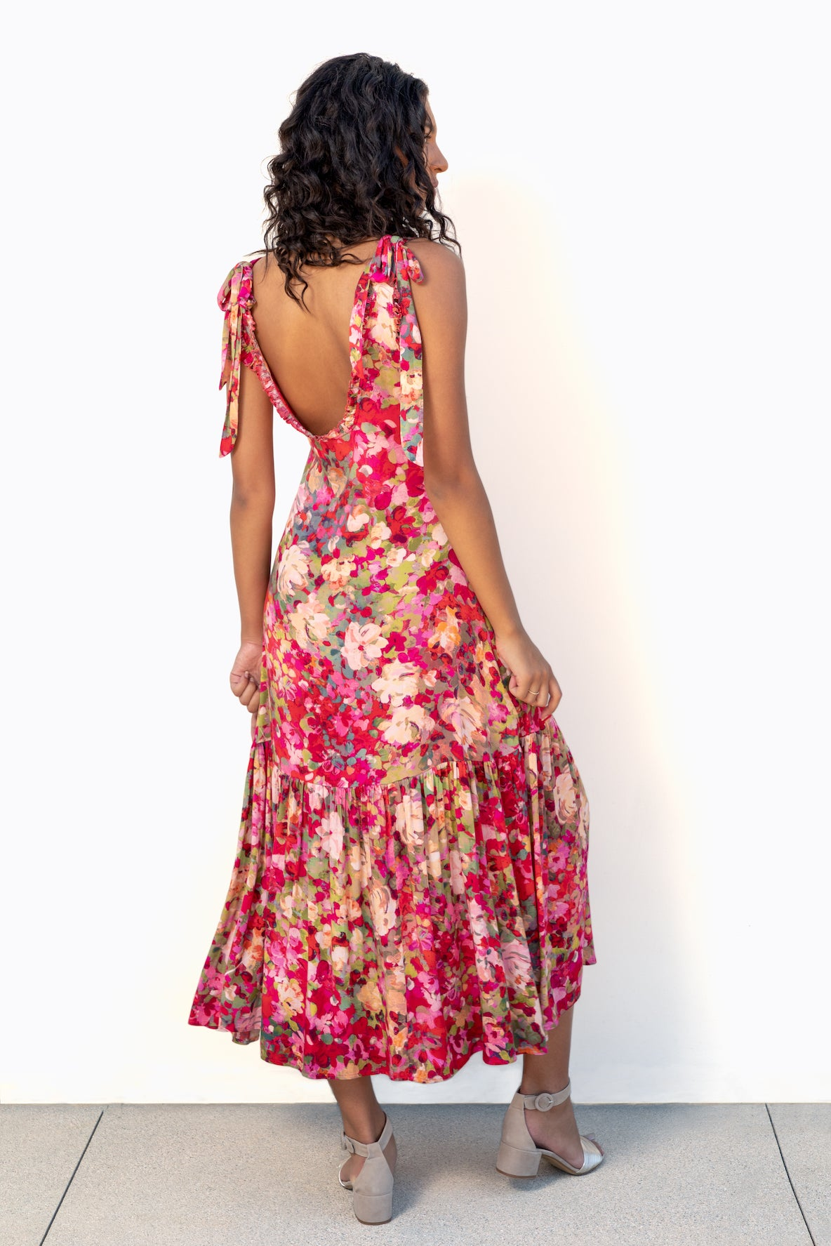 Back of model's full body wearing Finchley Camino's maxi length red floral dress with large ruffle hem, straps tied in bows, and a low back with a ruffle trim.
