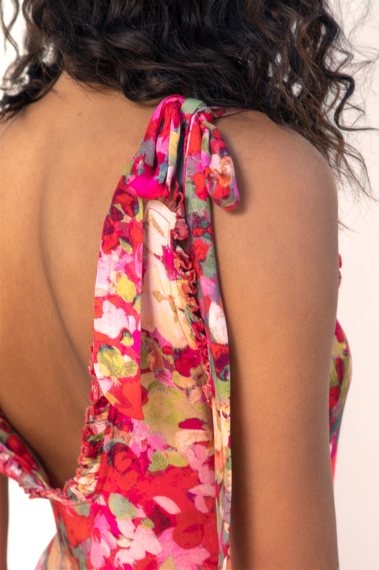 Close up of model's back wearing Finchley Camino's red floral dress with straps tied in a bow at the top of the shoulder and a low back with a ruffle trim