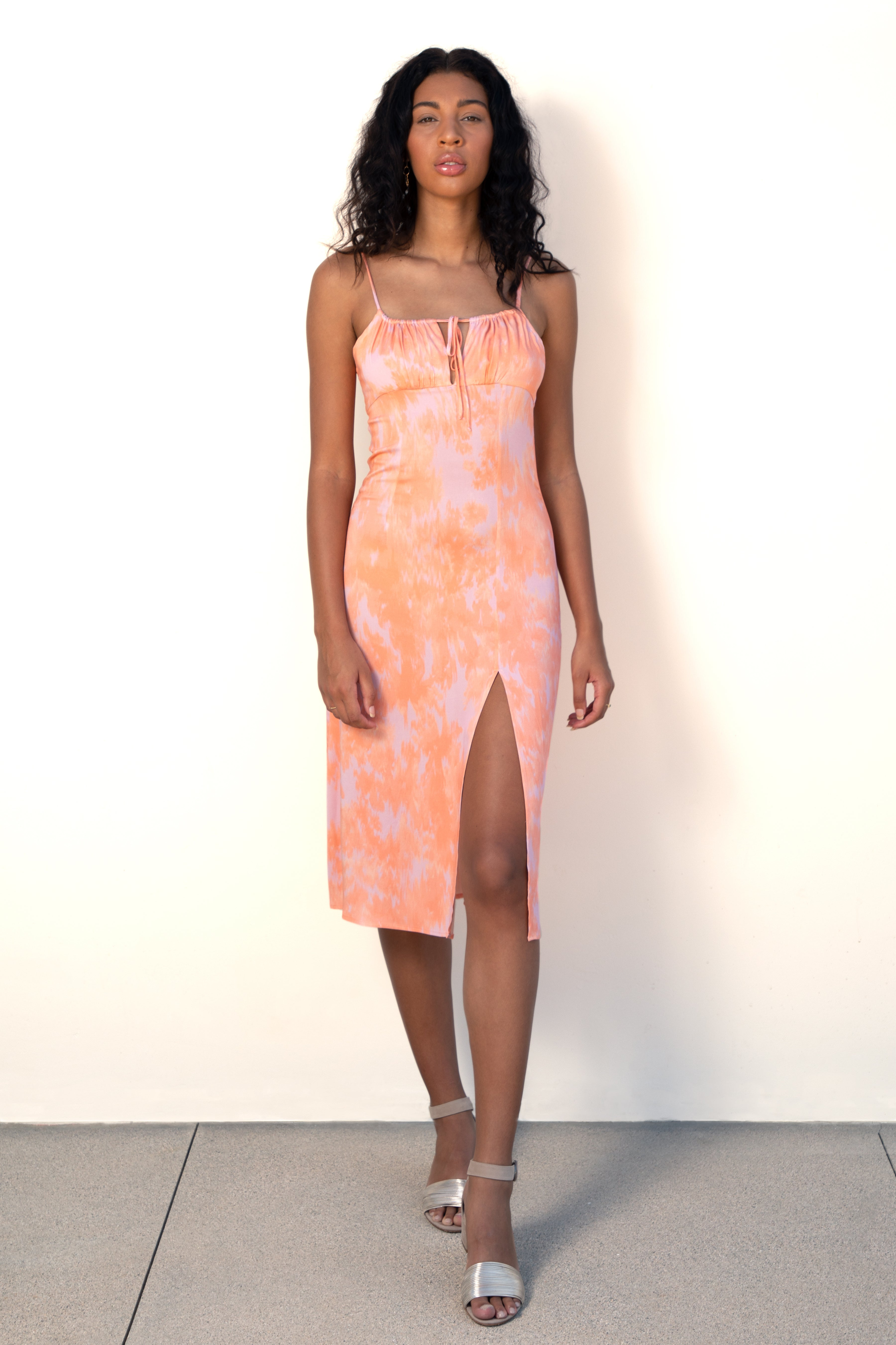Model wears LA fashion brand Finchley Camino's peach colored spaghetti strap midi dress with a ruched bust and a thigh high slit