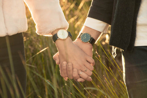 Couple holding hands in showcasing watches