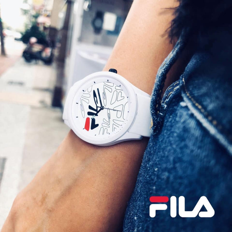 Female model wearing Picture of FILA | 38-129-204 | Men's and Women's White Analog Watch with White and Black Silicone Strap | Water Resistant and dark navy jeans