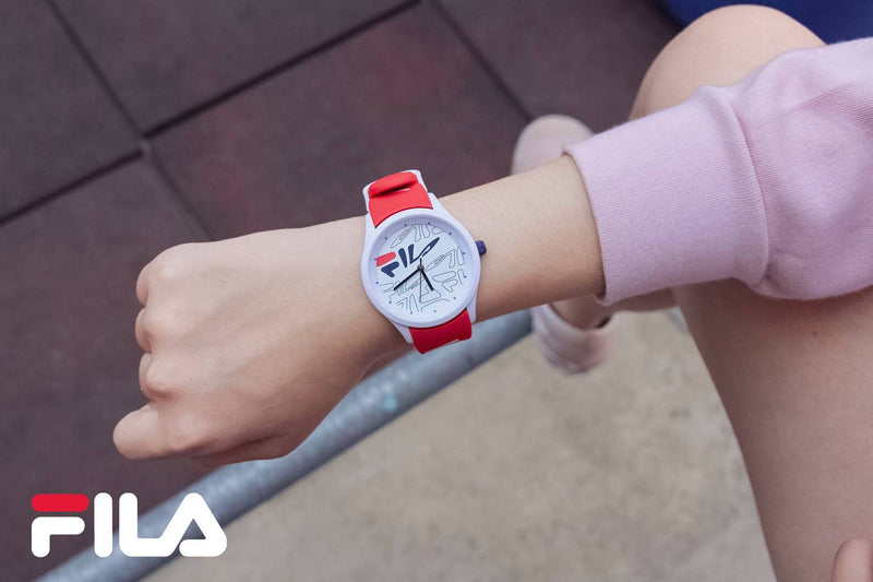 Model wearing FILA | 38-129-206 | Men and Women's White Analog Watch with Red and White Silicone Strap | Water Resistant with a pink sweater and pink shoes