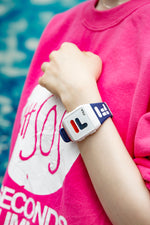 Female model wearing Fila's 38-105-005 timepiece with a hot pink sweater