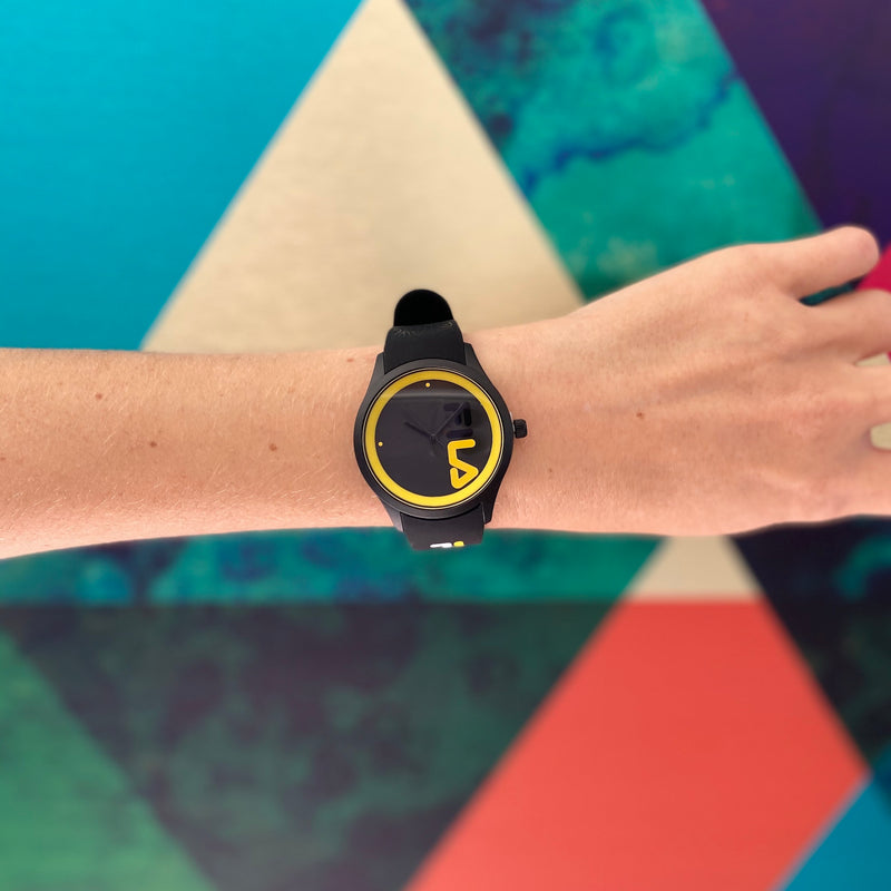 Model wearing FILA | 38-129-212 | Men and Women's Black and Yellow Analog Watch | Water Resistant in front of an artistic background