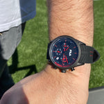Model wearing FILA | 38-176-001 | Men's and Women's Black Analog Watch | Date Tracker | Stopwatch with grey jeans and a white t-shirt