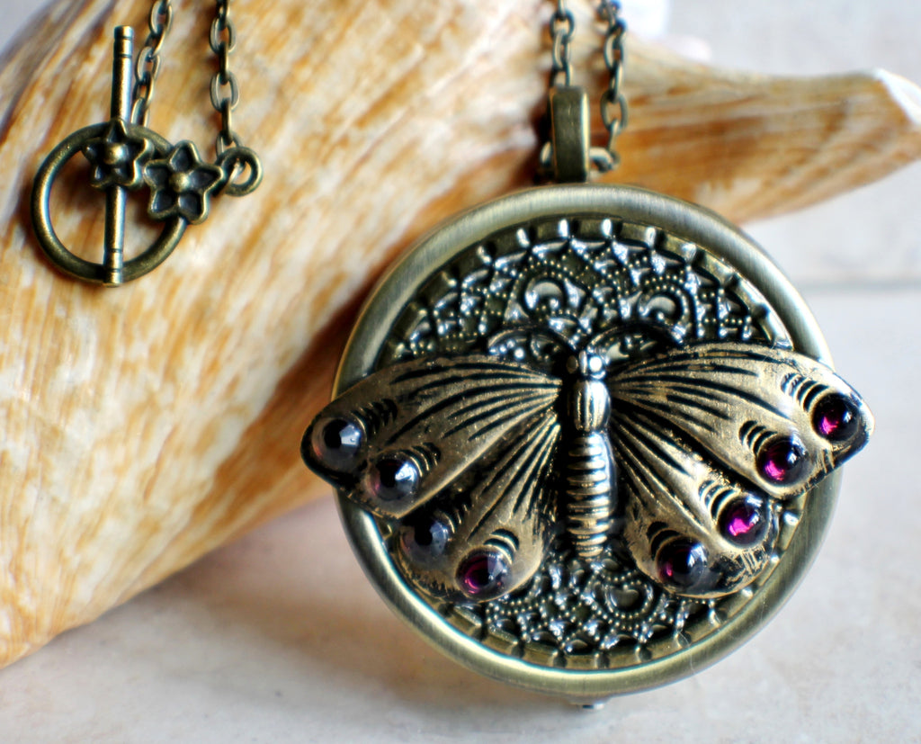 Music box locket,  round locket with music box inside, in bronze with filigree and butterfly adorning front cover. - Char's Favorite Things - 1