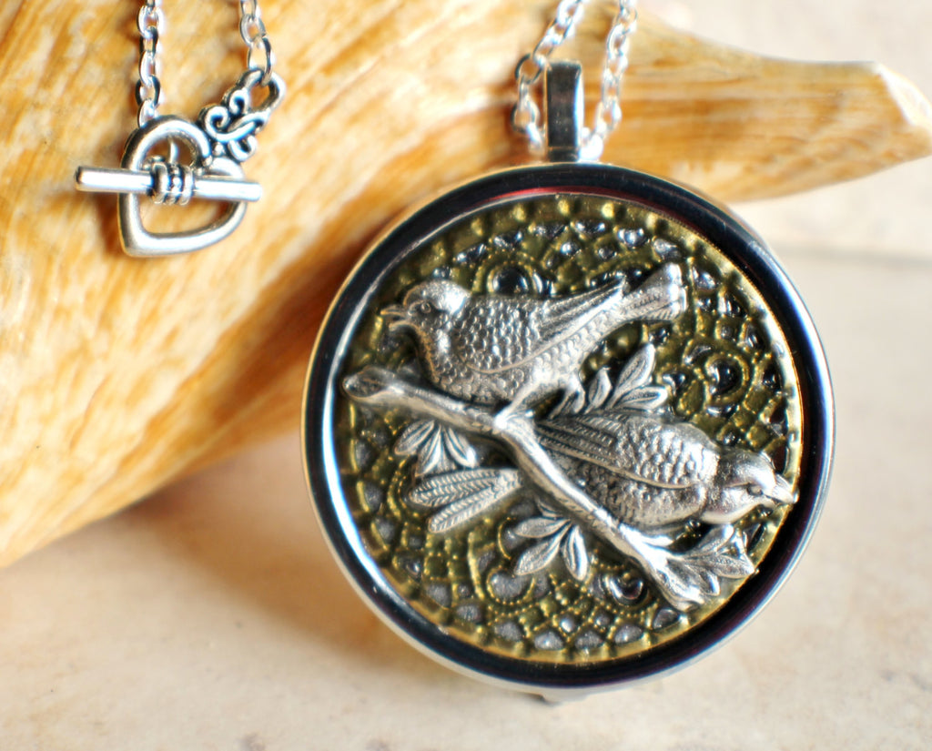 Bird music box locket, silvertone locket with music box inside, and birds on a branch on the front cover