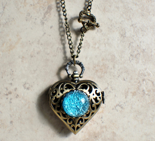 Heart watch locket with blue glass fire opal on front cover in bronze.