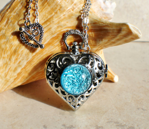 Heart watch locket with blue glass fire opal on front cover in silvertone.