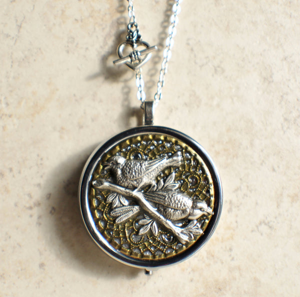 Round Bird music box locket in silver tone.