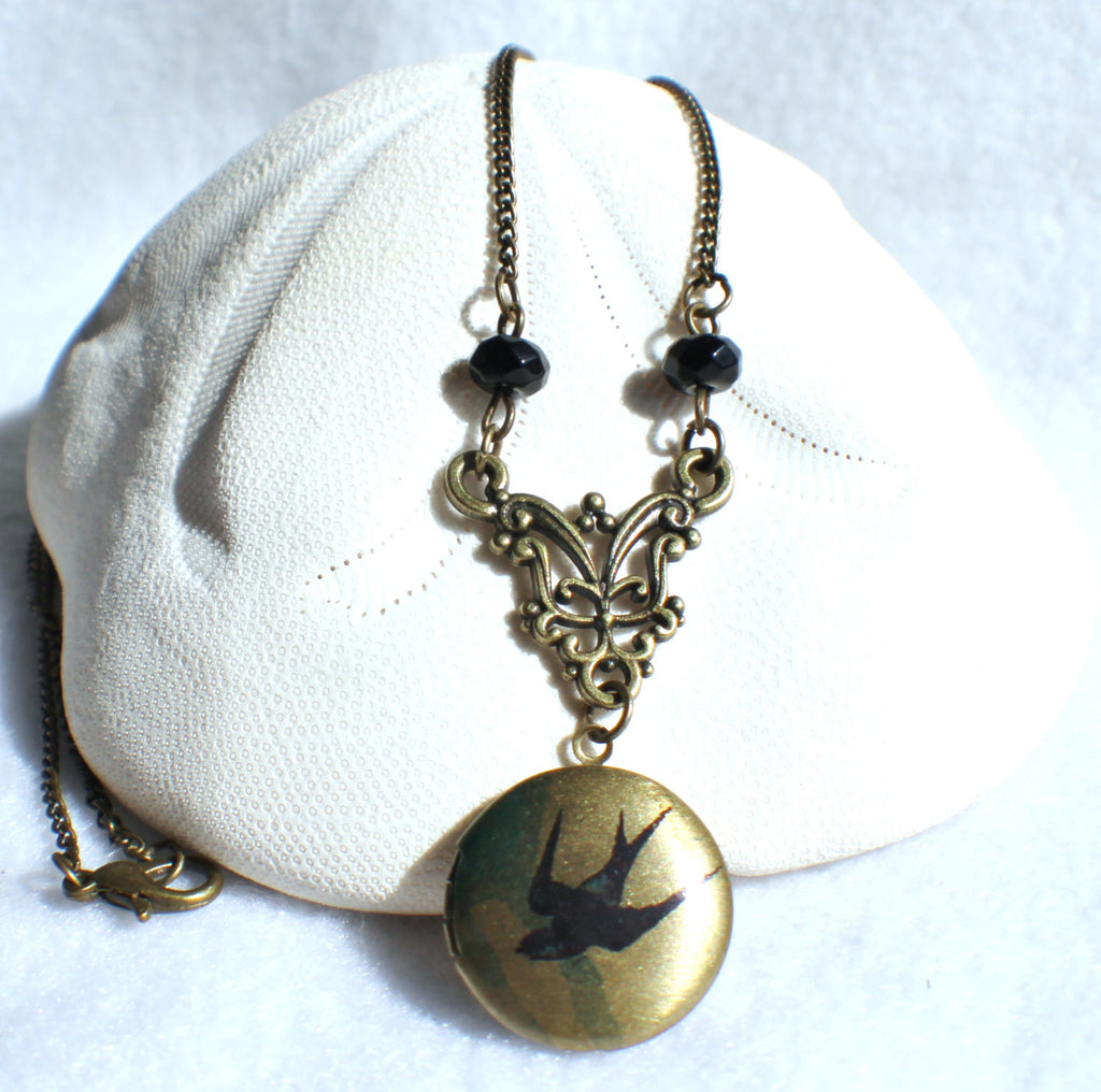 Round locket with bird on front cover adorned with black beads and bronze accents - Char's Favorite Things - 1