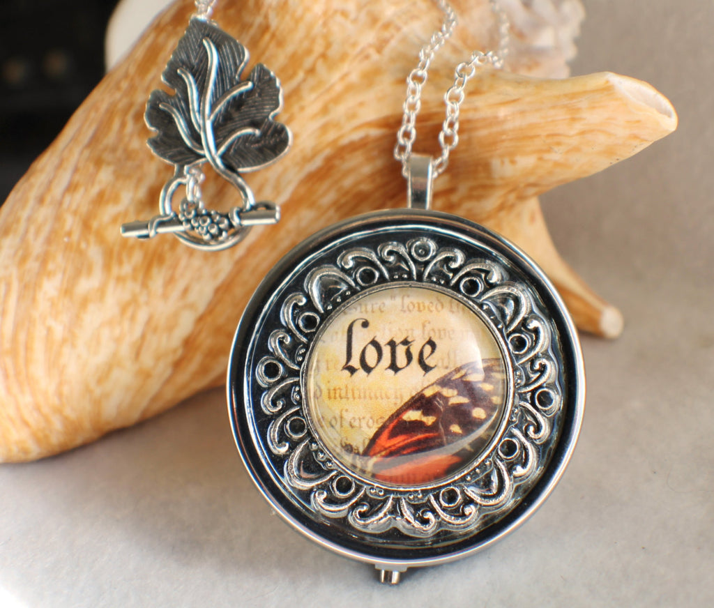 Music box locket, round locket with music box inside, in silver tone with Love and Butterfly Cabochon - Char's Favorite Things - 1