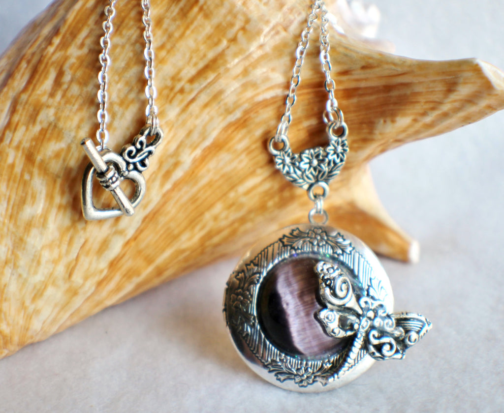Dragonfly photo locket, round silver tone locket with purple cats eye cabochon and silver dragonfly on front cover. - Char's Favorite Things - 1