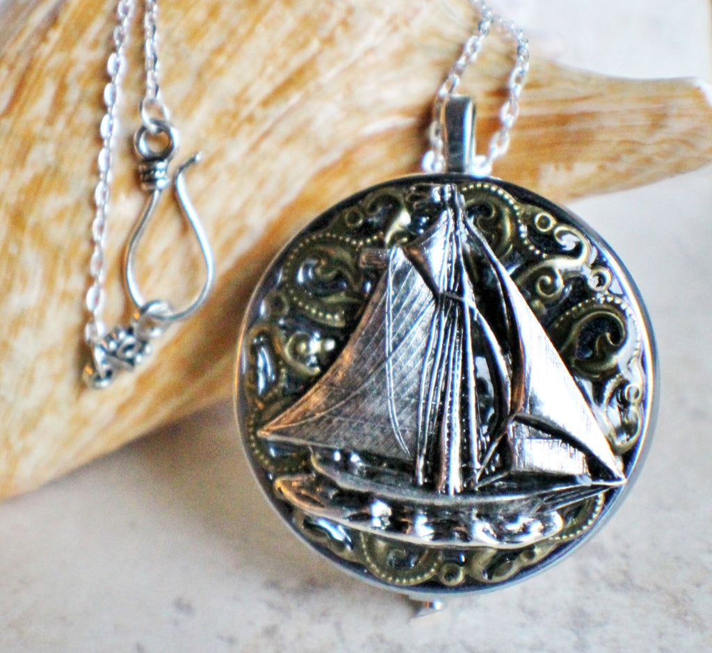 Music box locket, round silver tone locket with music box inside, with a nautical theme featuring a sailboat on front cover. - Char's Favorite Things - 1