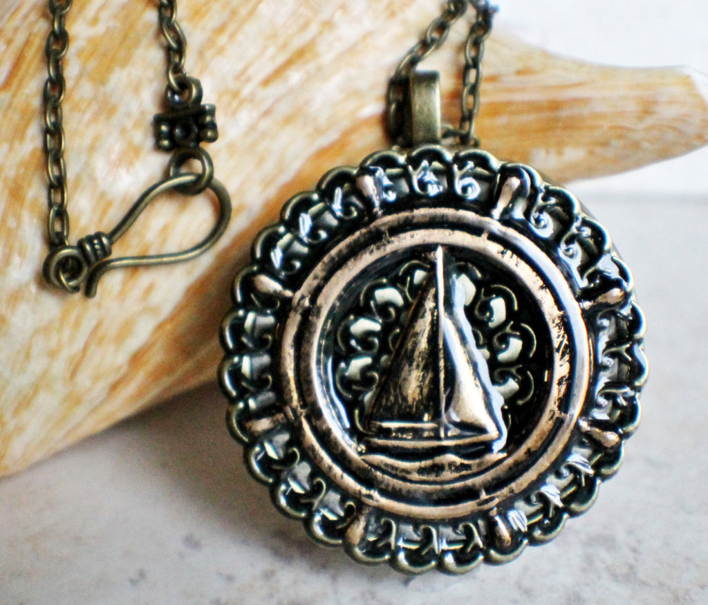Music box locket, round bronze locket with music box inside, with a nautical theme featuring a sailboat on front cover. - Char's Favorite Things - 1