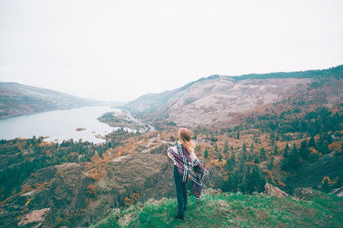 Photograph of a young woman taking in a gorgeous view on a chilly fall day