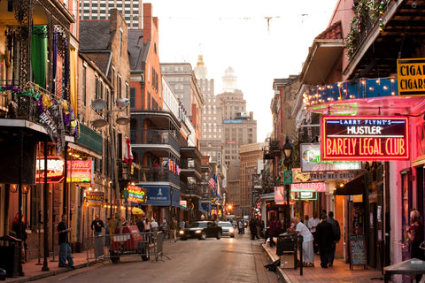 A lively view of Bourbon Street as the sunsets before the night begins in New Orleans, Louisiana.