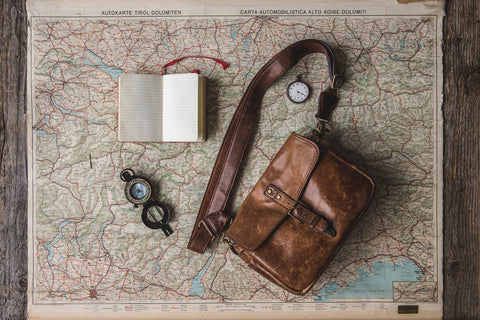 World map with a satchel and compass