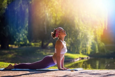 Young woman doing yoga in a park on a sunny spring day
