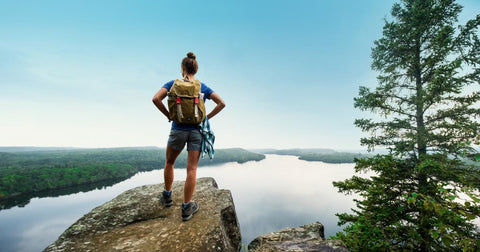 Young woman hiking up a mountain and looking at a beautiful view of a lake in the spring.