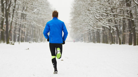 Young man running down a beautiful white snowy path in the winter