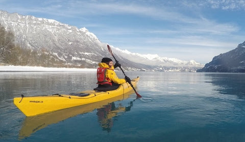 A gorgeous view of a man kayaking a lake in between snowy mountains on a sunny winter day.