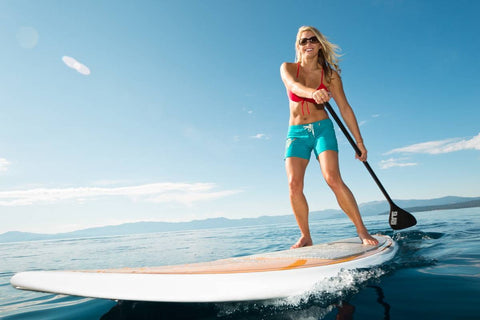 Young blonde woman paddle boarding in Miami, Florida on a beautiful sunny day in the summer.