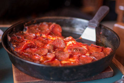 Pequod's is a Chicago favorite with their unique crust; The caramelized halo crust is created by sprinkling mozzarella edge to edge and baking it until it's crispy and brown.