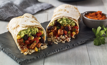 A hearty burrito full of green veggies and protein