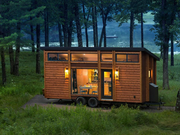Beautiful tiny home in the forrest on a lake at dusk.