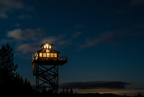 Night time view of a beautiful tree house on the water in Tiller Oregon