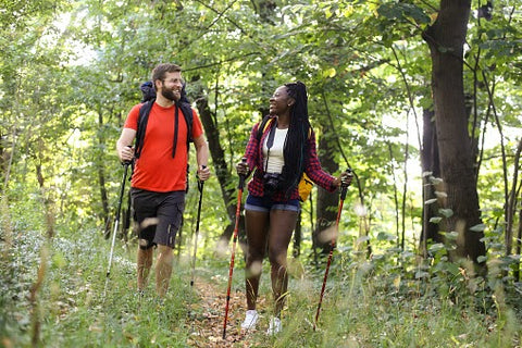 Happy couple hiking through the mountains on a warm summer day