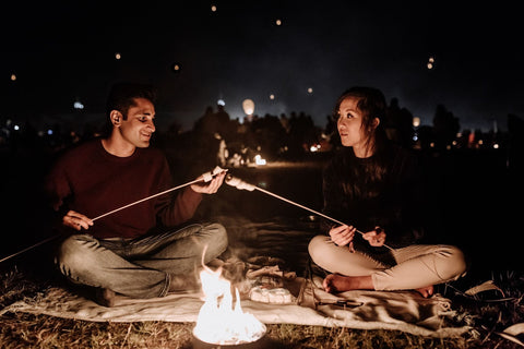 Loving couple roasting marshmallows over a campfire on a warm summer night