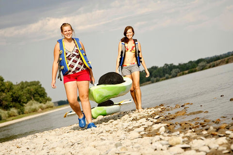 Happy couple preparing the kayak to hit the lake for a day in the sun