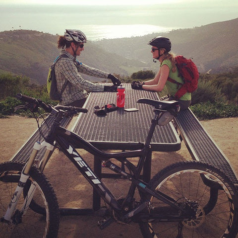Happy couple taking a rest stop after a long day of mountain biking